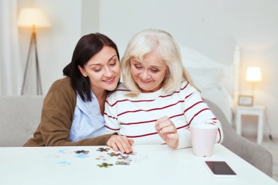 caregiver help the elderly form a puzzle