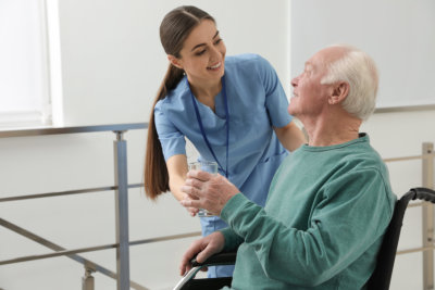 Nurse giving water to senior men in wheelchair at hospital. Medical assisting