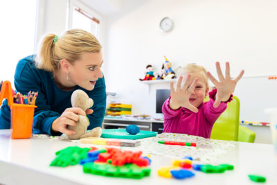 Toddler girl in child occupational therapy session doing sensory playful exercises with her therapist