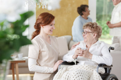 Older women sits on wheelchair next to nurse and is holding a cup of coffee
