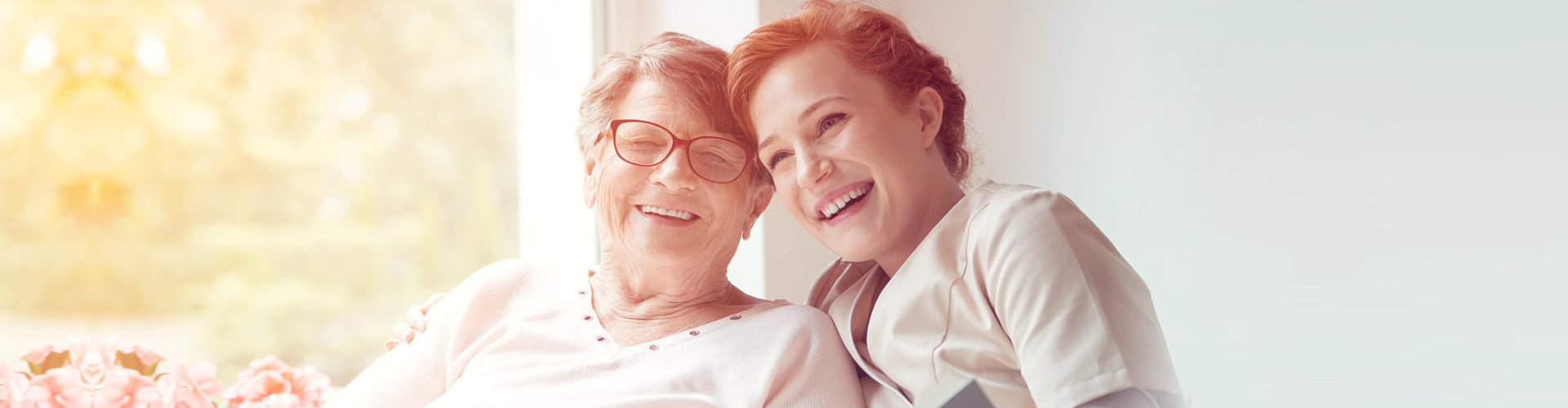 caregiver and an elderly woman smiling at the camera