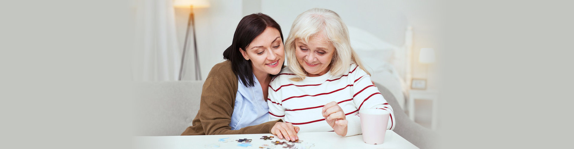 caregiver helps the elderly form a puzzle