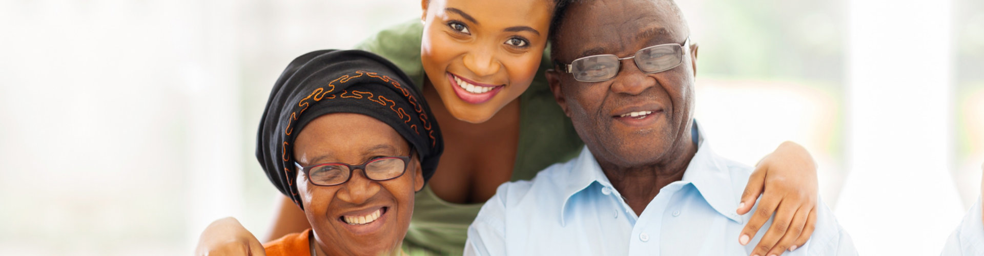 caregiver and an elderly couple smiling at the camera